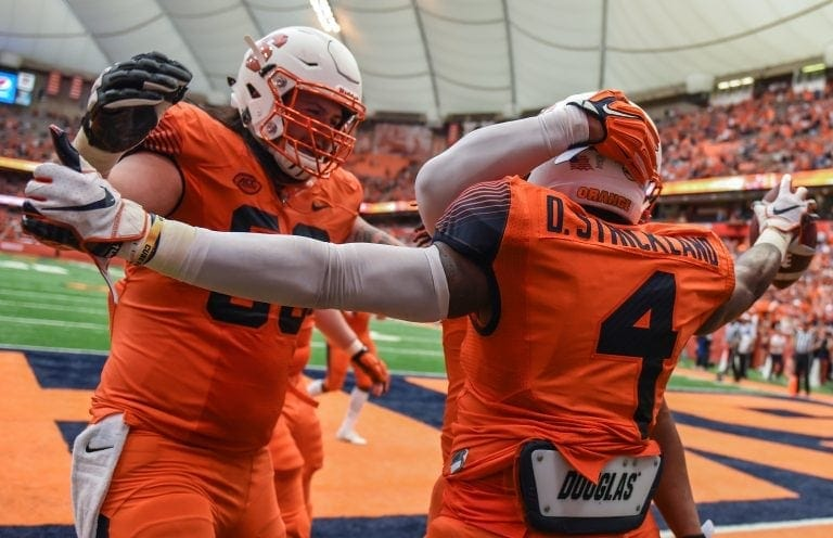 Syracuse University running back Dontae Strickland (4) celebrates a touchdown with his teammates during the Orange's 30-7 win over Florida State.
