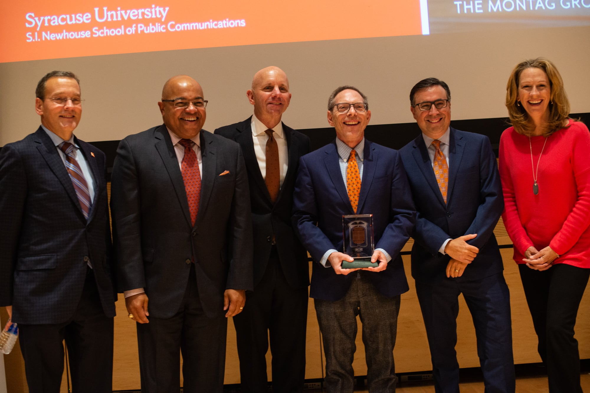 2019 Marty Glickman Award Sandy Montag (third from right) is joined by Syracuse Athletic Director John Wildhack and preview Glickman winners Mike Tirico, Sean McDonough, Ian Eagle and Beth Mowins.