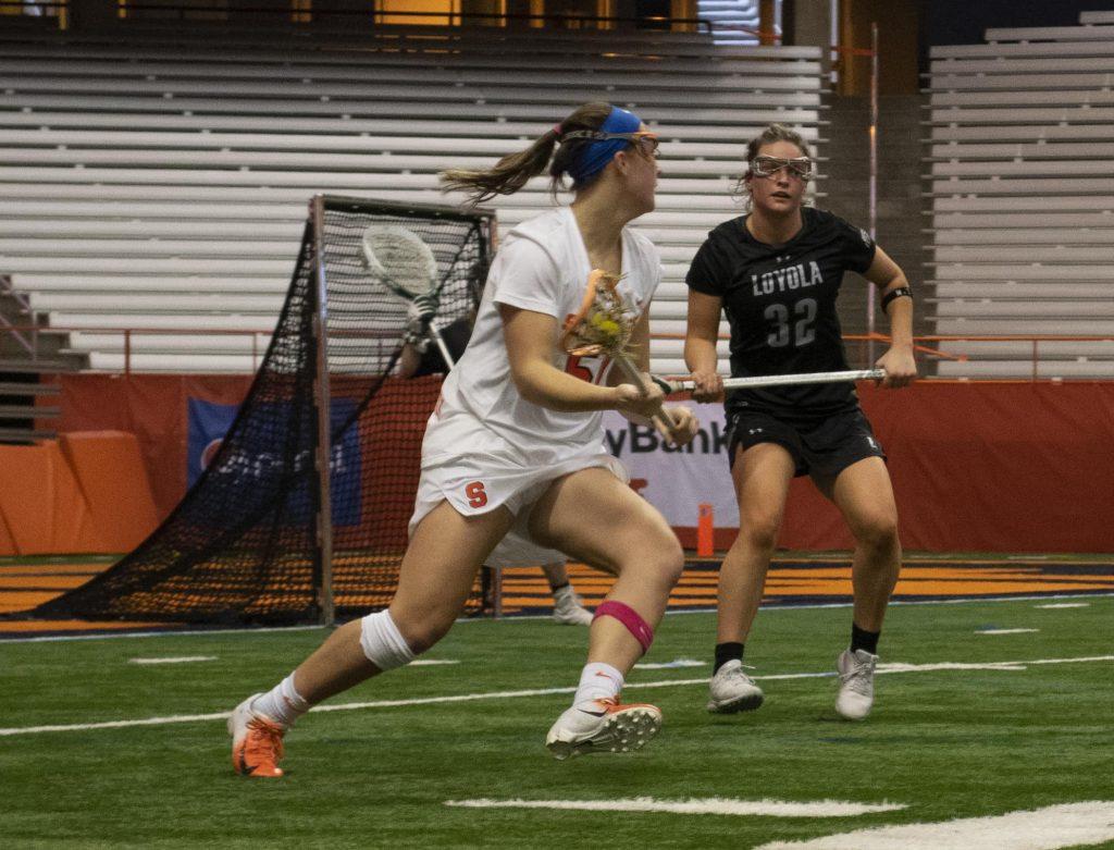 Syracuse's Emily Hawryschuk takes on Loyola Maryland defender Katie Detwiler.