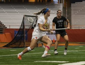 Syracuse's Emily Hawryschuk takes on Loyola Maryland defender Katie Detwiler.