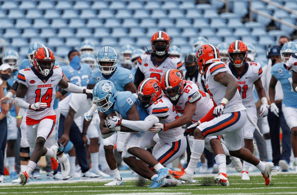 Syracuse defenders swarm to bring down UNC's Michael Carter (8) in first half action in Kenan Stadium Saturday, September 12, 2020 in Chapel Hill, N.C. Fans have been prohibited from attending the game due to the COVID-19 virus.