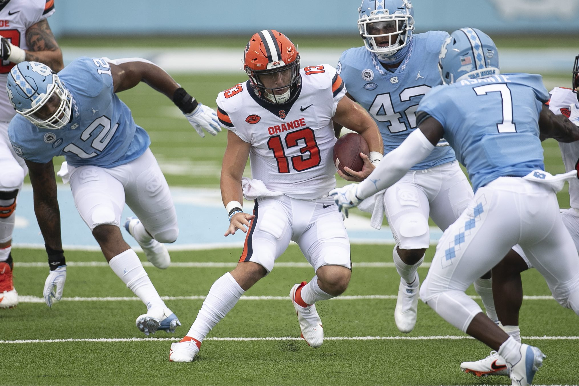 Syracuse quarterback Tommy DeVito (13) looks for running room against North Carolina's Eugene Asanti (7) during the second quarter in Kenan Stadium on Saturday, September 12, 2020 in Chapel Hill, N.C.
