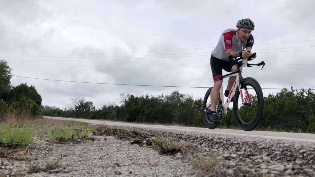 Paratriathlete Ulf Oesterle riding his bike on a Syracuse area road.