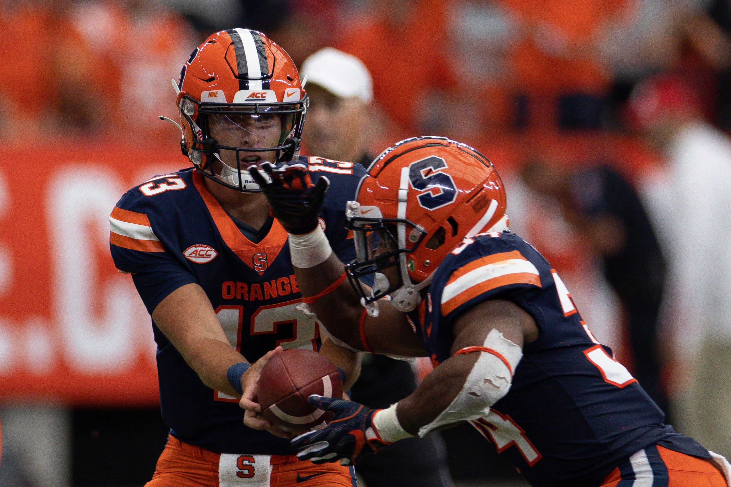 Syracuse's Tommy DeVito (13) hands the ball off to Sean Tucker during an NCAA football game against Rutgers, Saturday, at the Carrier Dome.