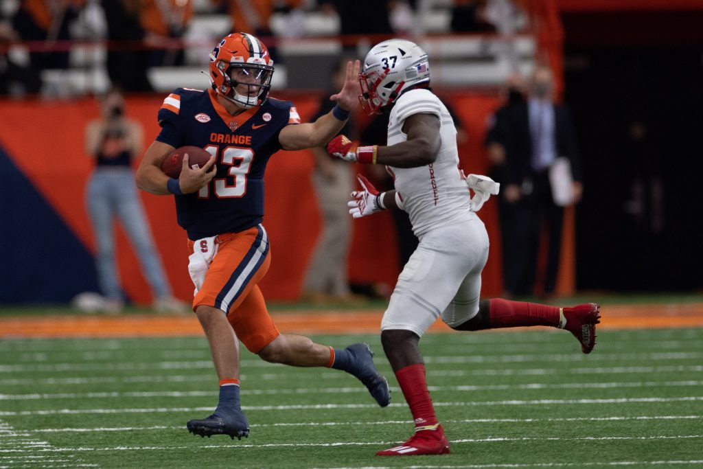 Syracuse's Tommy DeVito (13) stiff-arms Avery Young as he runs upfield during an NCAA football game against Rutgers, Saturday, at the Carrier Dome.