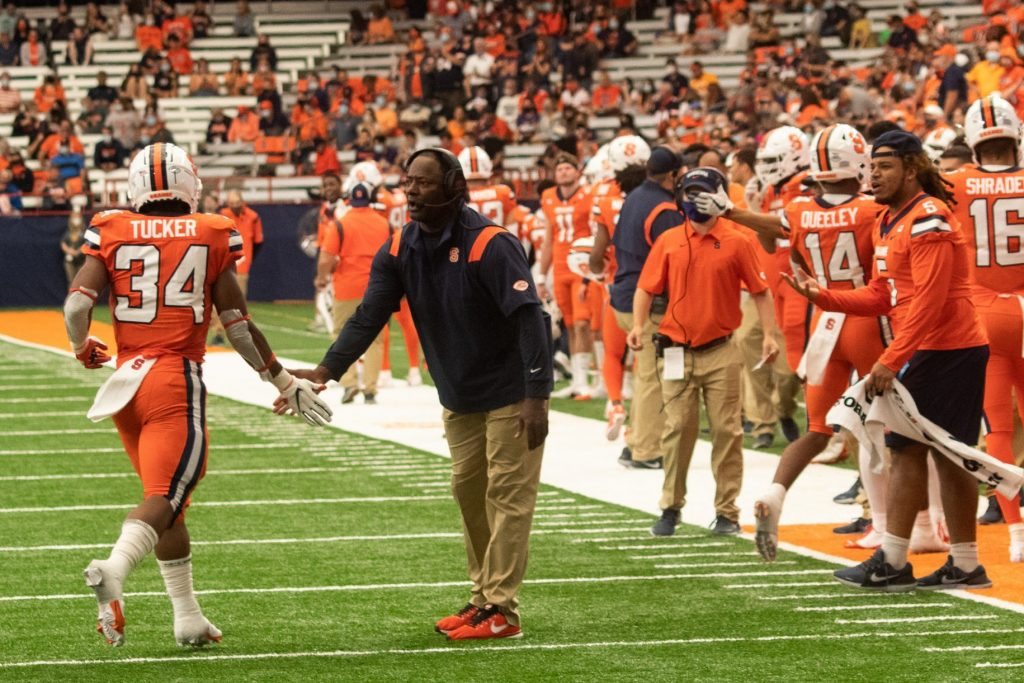 Syracuse University football coach Dino Babers high fives Sean Tucker (34) as Tucker returns to the sidelines during a NCAA football game against University of Albany, Saturday, at the Carrier Dome.