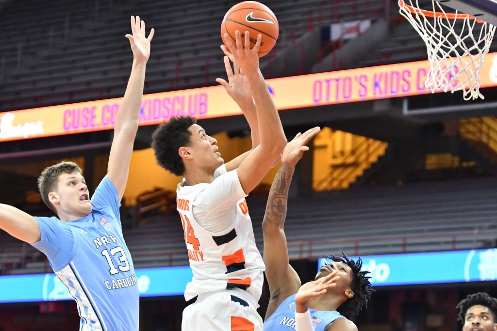 Mar 1, 2021; Syracuse, New York, USA; Syracuse Orange center Jesse Edwards (14) shoots near the basket as North Carolina Tar Heels forward Walker Kessler (13) and guard Caleb Love (bottom) defend in the first half at the Carrier Dome. Mandatory Credit: Mark Konezny-USA TODAY Sports