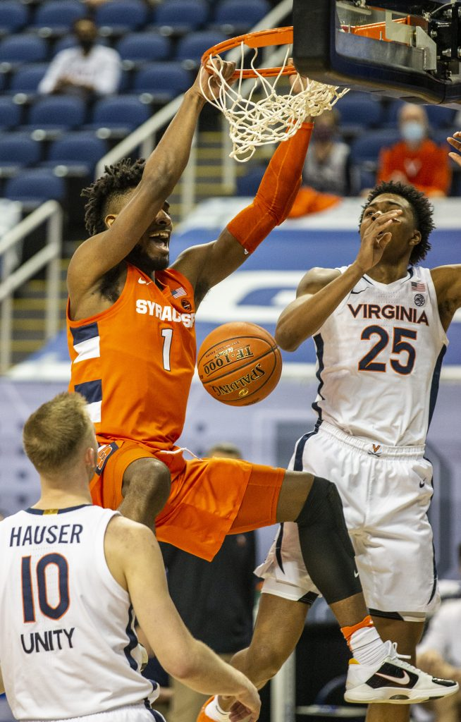 Quincy Guerrier (1) dunks over Virginia defenders in Greensboro, N.C., on Thursday, March 11, 2021.