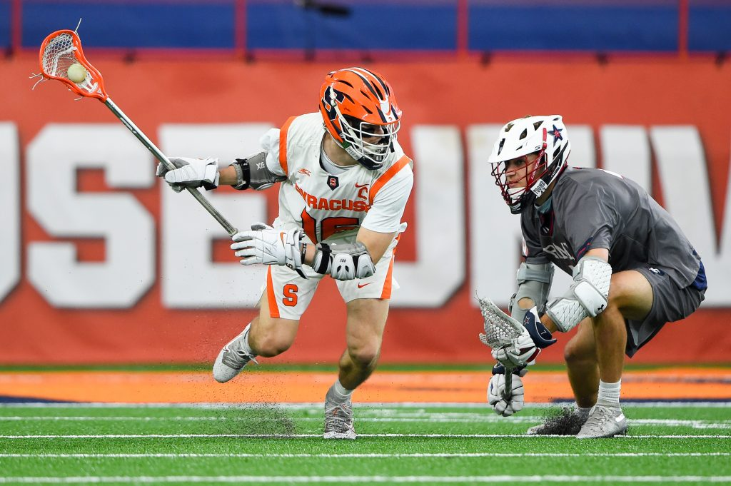 Brendan Curry #16 of the Syracuse Orange dodges to the goal against the defense of Blake Lori #7 of the Robert Morris Colonials during the first half at the Carrier Dome.