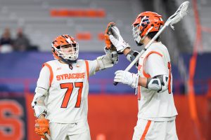 Owen Hiltz #77 of the Syracuse Orange celebrates a goal with teammate Owen Seebold #14 against the Robert Morris Colonials during the second half at the Carrier Dome.