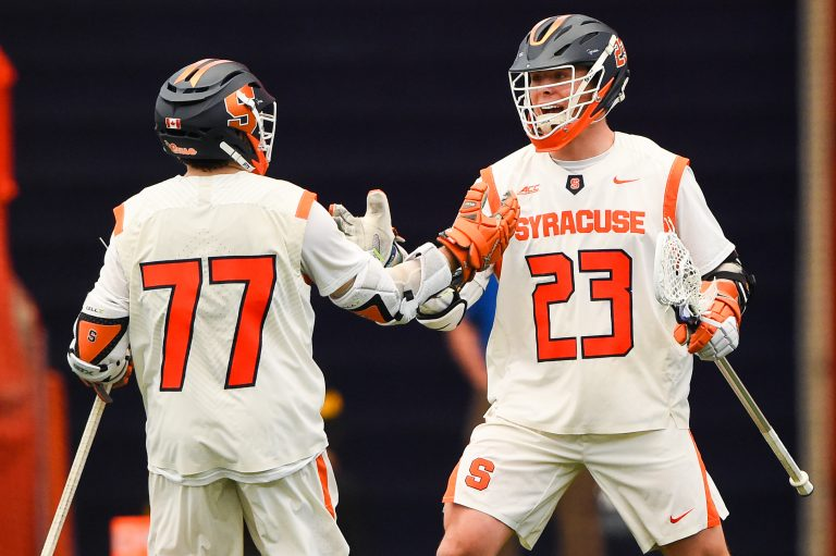 Mar 12, 2021; Syracuse, New York, USA; Syracuse Orange attackman Owen Hiltz (77) and midfielder Tucker Dordevic (23) celebrate a goal against the Stony Brook Seawolves during the first half at the Carrier Dome. Mandatory Credit: Rich Barnes