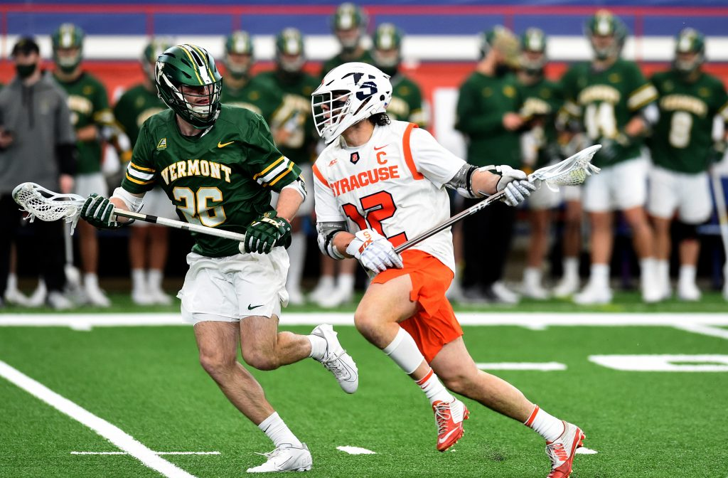 #12 Jamie Trimboli of Syracuse runs past Vermonts # 20 Dobson Cooper in a game between Syracuse and Vermont at the Carrier Dome.