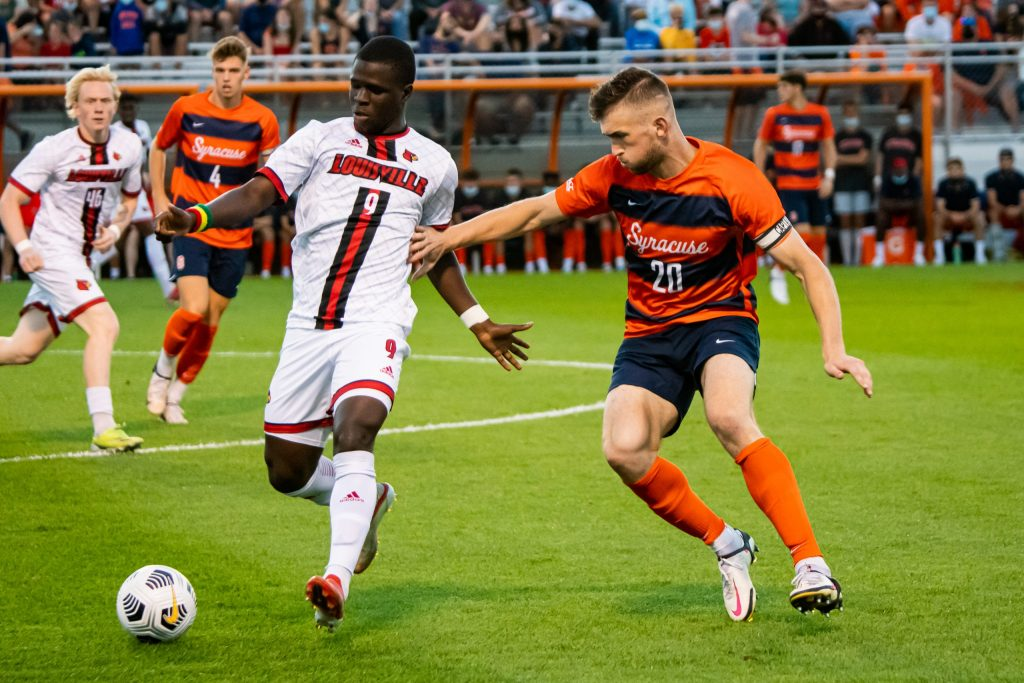 Louisville's Aboubacar Camara (9) has control of possessoin as he winds up for a pass with Syracuse's Max Kent (20) crashing down to defend.
