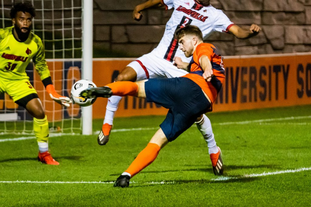 Syracuse's Giona Leibold strikes a shot with his left foot toward the goal and Louisville keeper Detre Bell, as Louisville's Dante Huckby (2) tries to deflect, during a men's soccer game, Friday, in Syracuse.