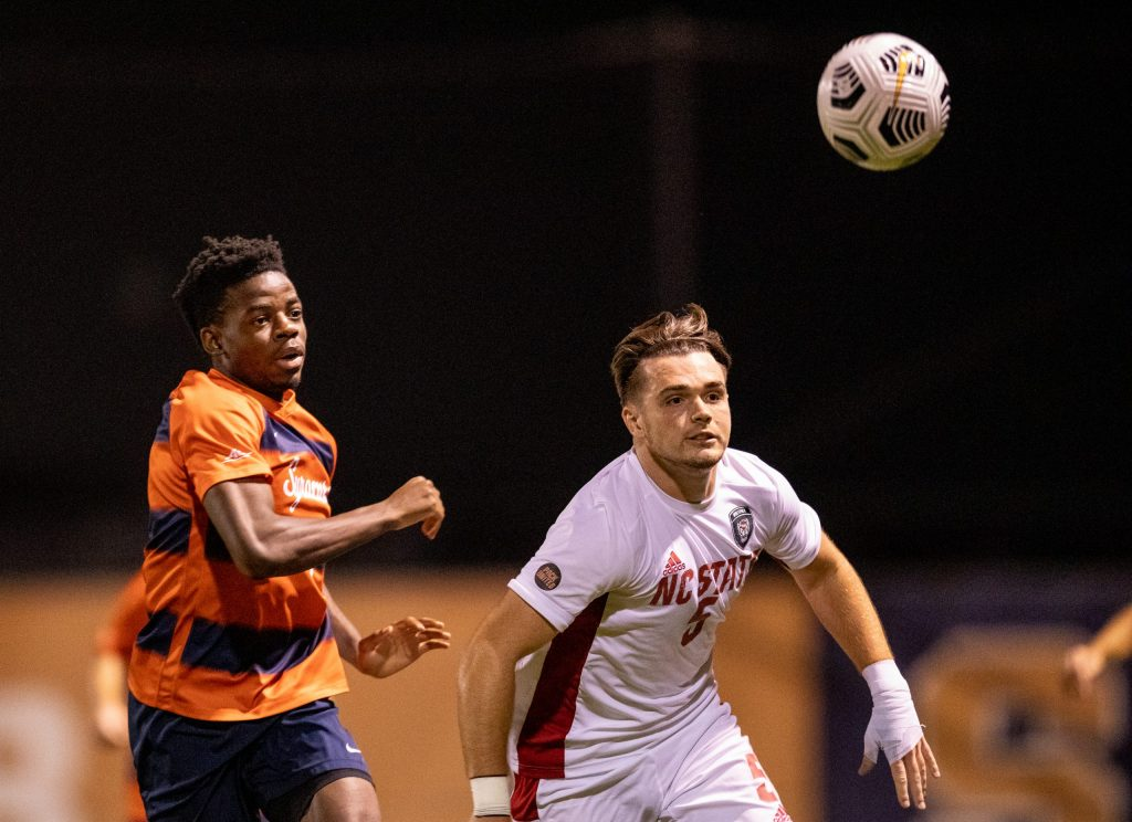 Syracuse's Julio Fulcar races NC State's Jamie Smith to the ball on Friday.