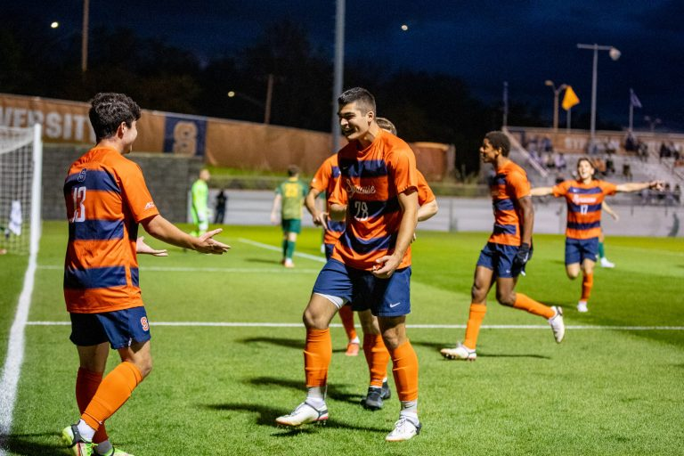 Colin Biros (13) celebrates with his teammates after scoring Syracuse's first goal during the Syracuse University Men's Soccer game vs UVM.