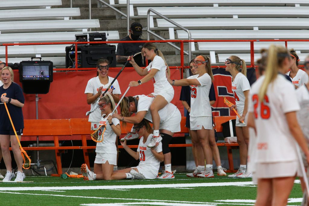The Syracuse sideline poses in celebration during a 20-8 victory over Loyola in the NCAA Tournament.