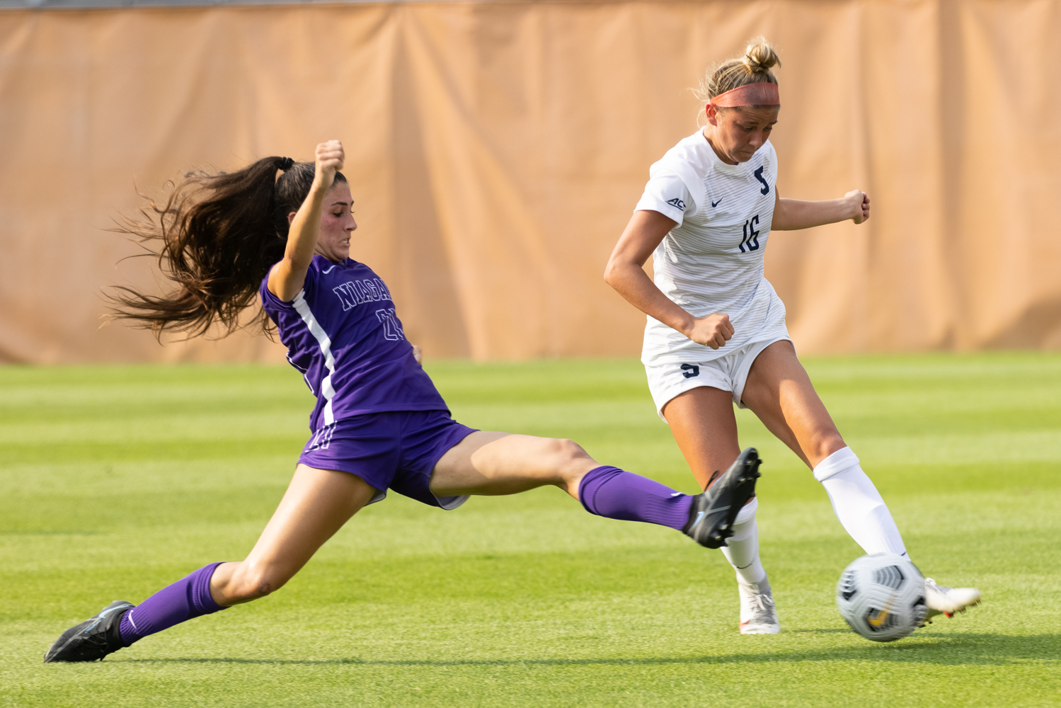 Niagra's Ida Miceli comes flying in for a slide tackle to try and take possession away from Syracuse's Koby Commandant (16) during an NCAA women's soccer game, Thursday, at Syracuse Soccer Stadium. Niagara defeated Syracuse, 4-2