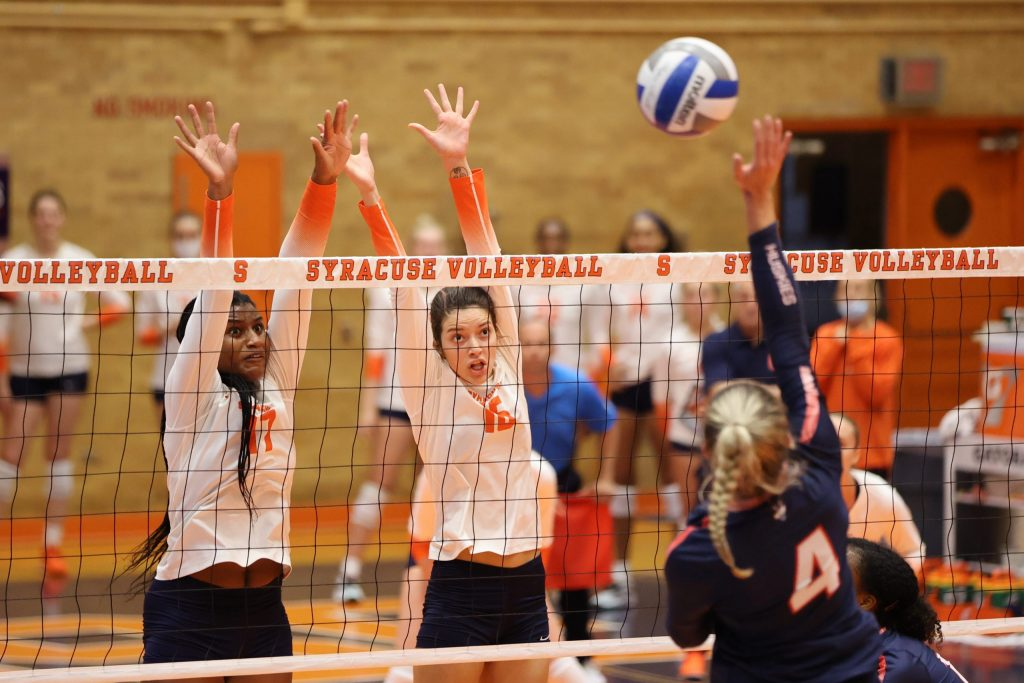 Syracuse's Naomi Franco and Abby Casiano attempt a block against University of Connecticut's Caylee Parker during the first set on August 27, 2021.