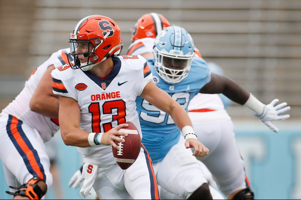Syracuse quarterback Tommy DeVito (13) scrambles to avoid UNC defender Jahlil Taylor (52) in first half action against North Carolina at Kenan Stadium on Saturday, September 12, 2020 in Chapel Hill, N.C.