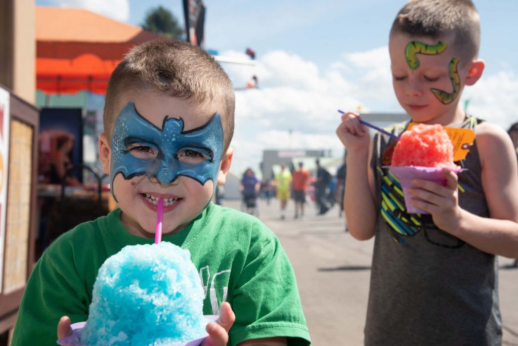 Ben Burkett (left) and his brother Noah Burkett eat Hawaiian Shaved Ice while visiting The Great New York State Fair