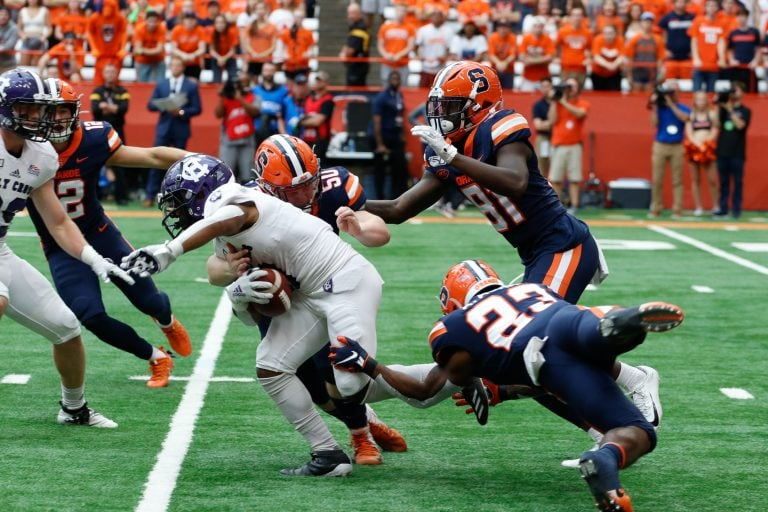 The Syracuse University defense works together to gain possession of the ball in the game against The College of the Holy Cross
