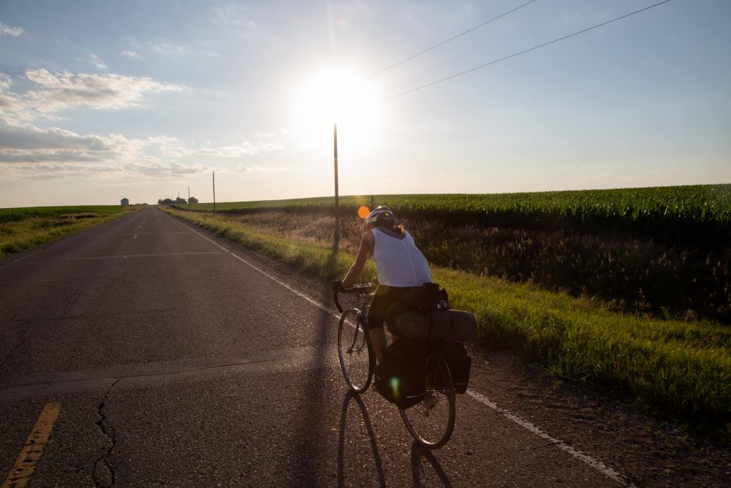 Abby Pershing, 23, biking with her pannier fastened to the back of her bike while riding on the side of I-20 in Iowa.