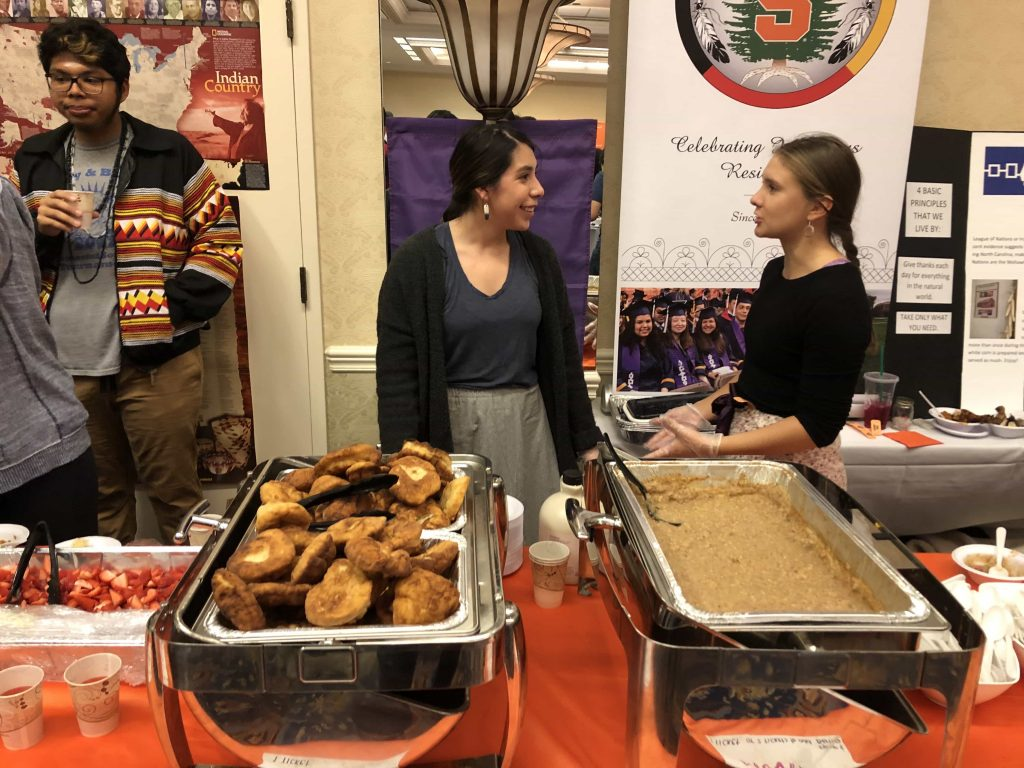 Rhiannon Abrams speaking with fellow indigenous student in front of fry bread and corn mush.