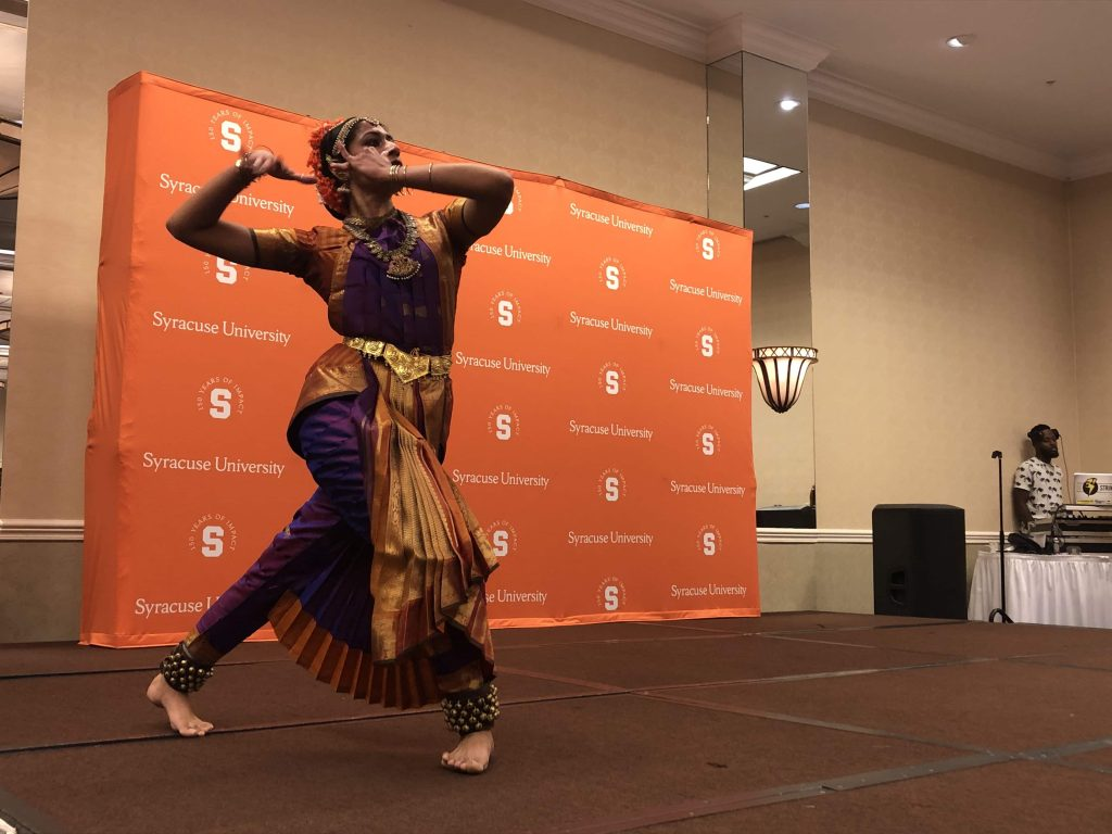 Syracuse student dressed in traditional Bharatanatyam attire dances on stage.