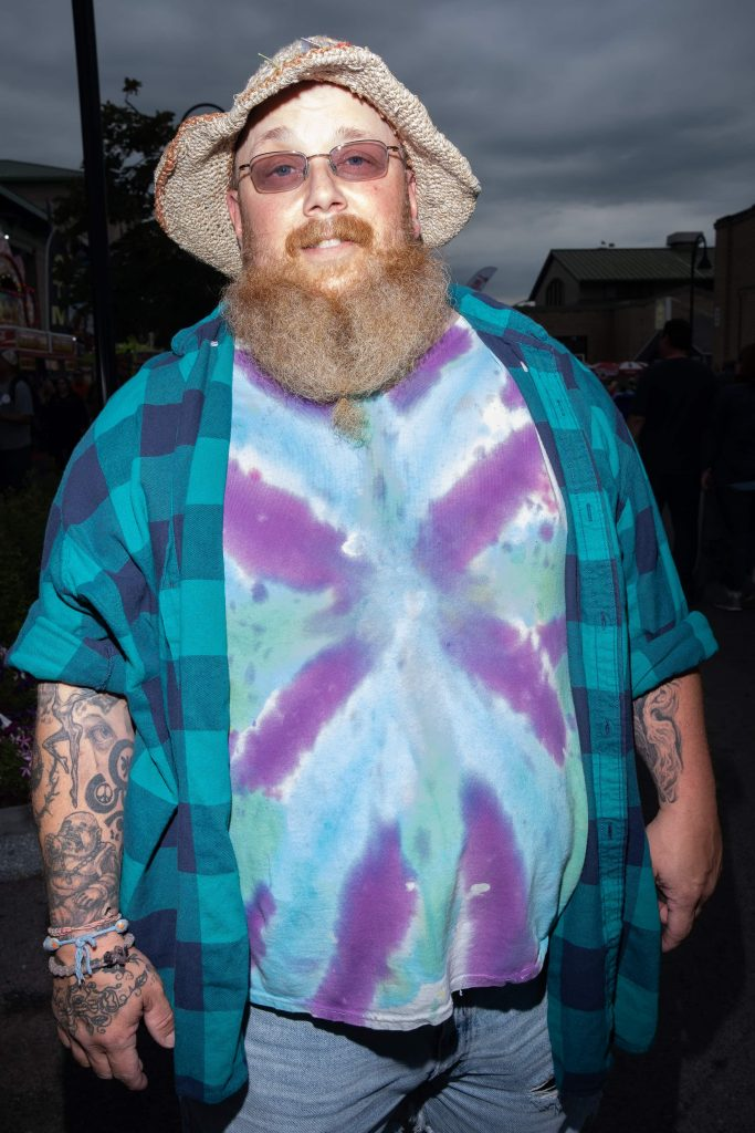 Dave Mondore's poses for a portrait at the New York State Fair, wearing bright tye-dye with matching flannel and sunglasses, as well as a burlap hat