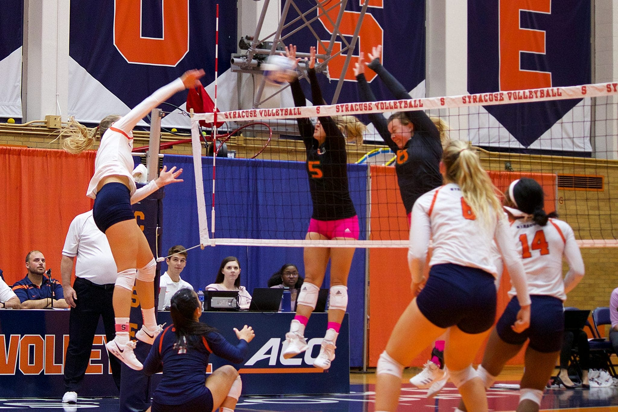 Syracuse spikes the ball on Miami defenders Friday during the Orange's 3-1 conference win.