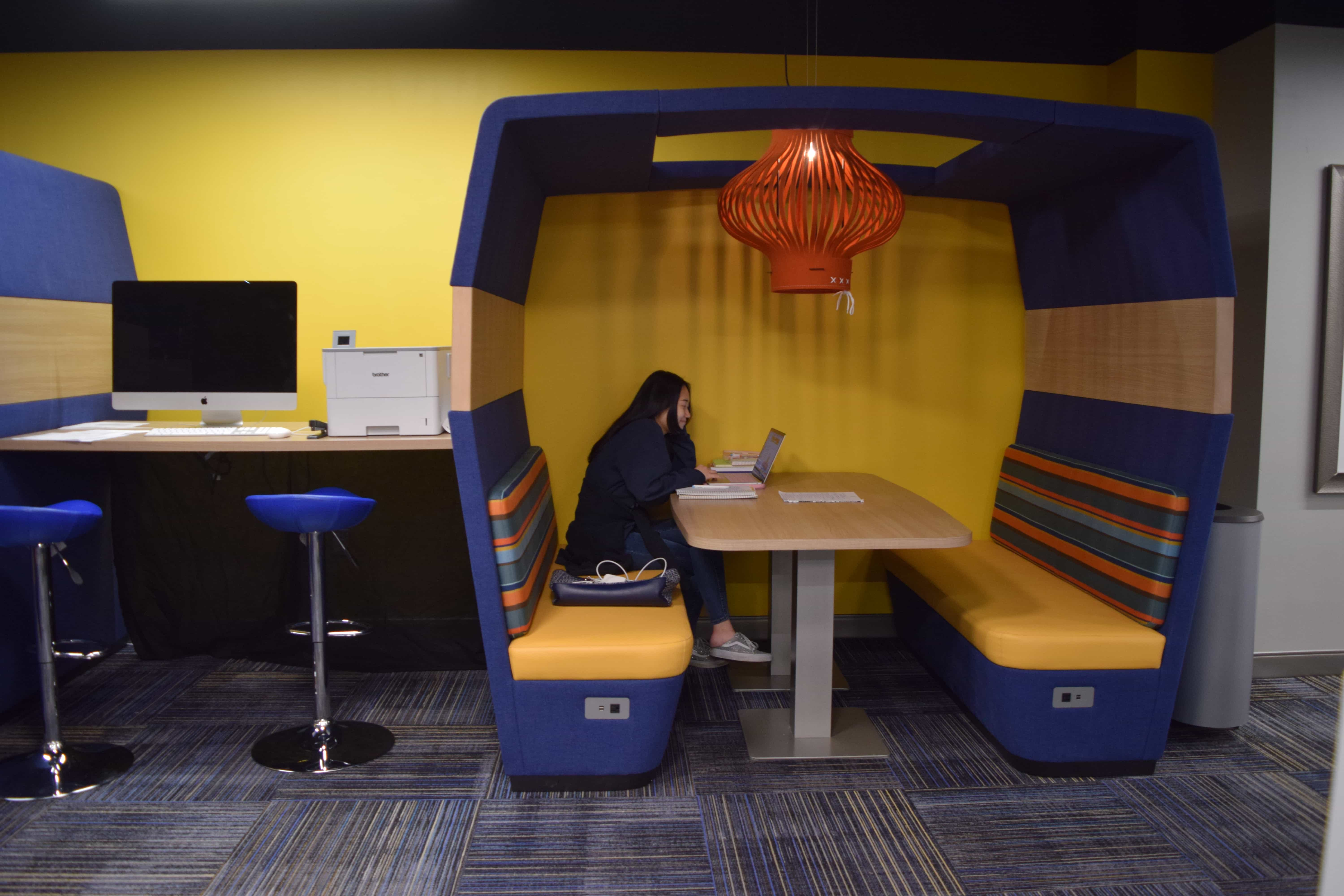 A female student sits in a covered booth with an orange and blue color-scheme.