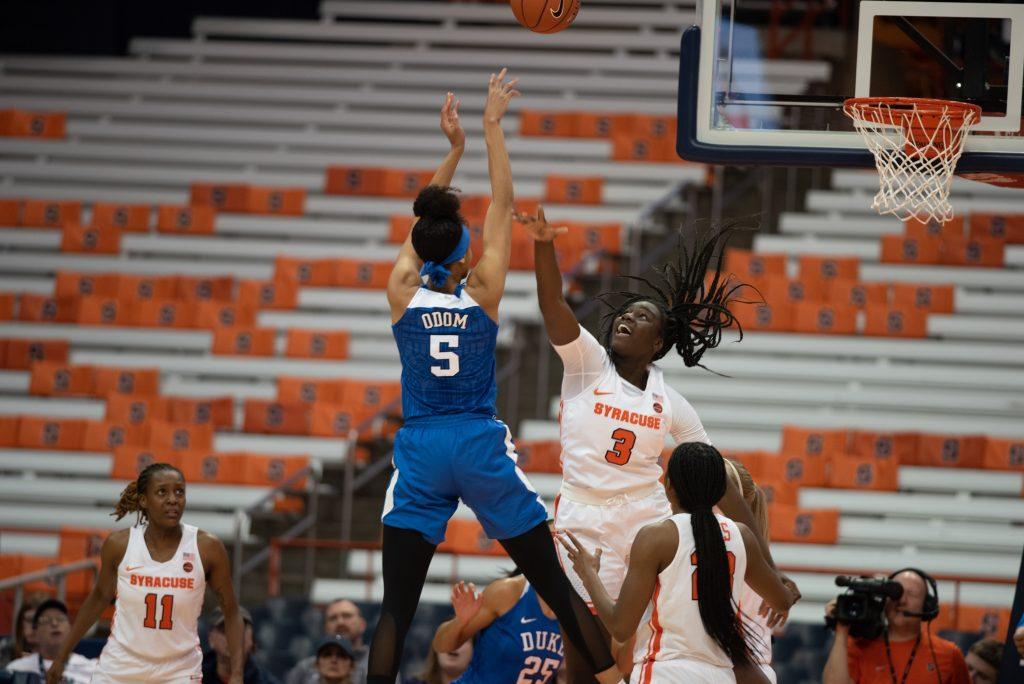 Forward Leaonna Odom, 5, breaks through Syracuse's defense despite Orange Forward Maeva Djaldi-Tabdi's best efforts during the game against Duke.
