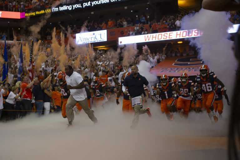 Dino Babers leads the Syracuse football team out to the stadium at Syracuse University's Carrier Dome on Sept. 14, 2019.