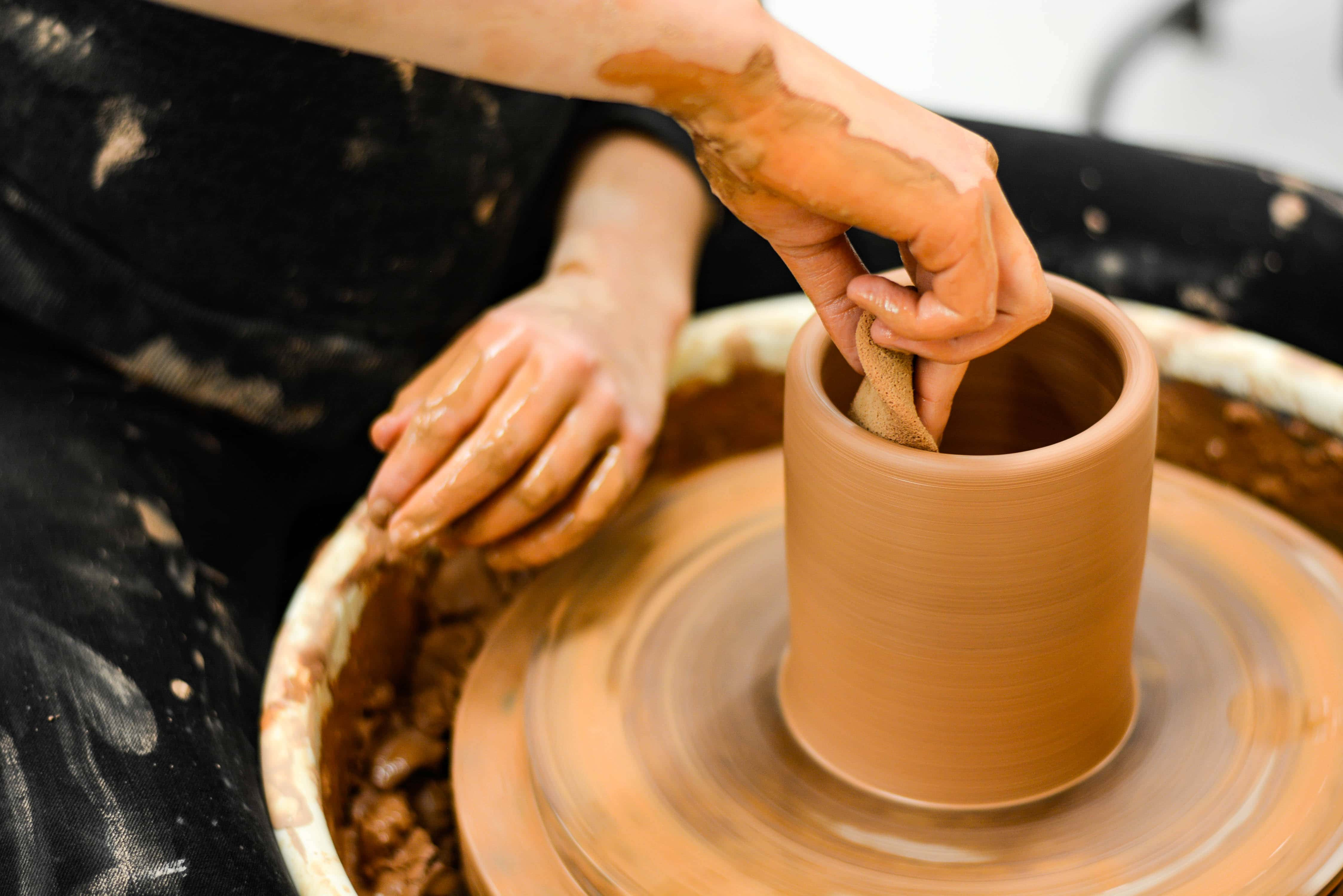 Ceramicist Isabel Souza throws a pot in the ComArts Studio on South Campus.