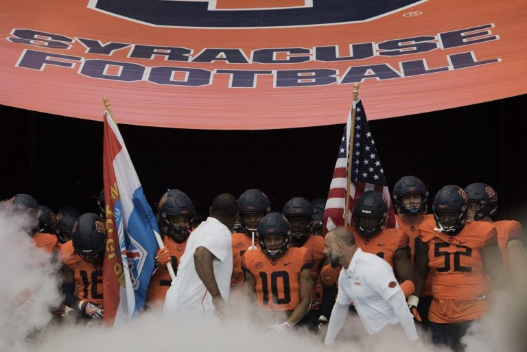 Head coach Dino Babers (left in white shirt) and his Orange football team prepares to run onto the Carrier Dome field prior to the Syracuse-Connecticut football game on Sept. 22, 2018