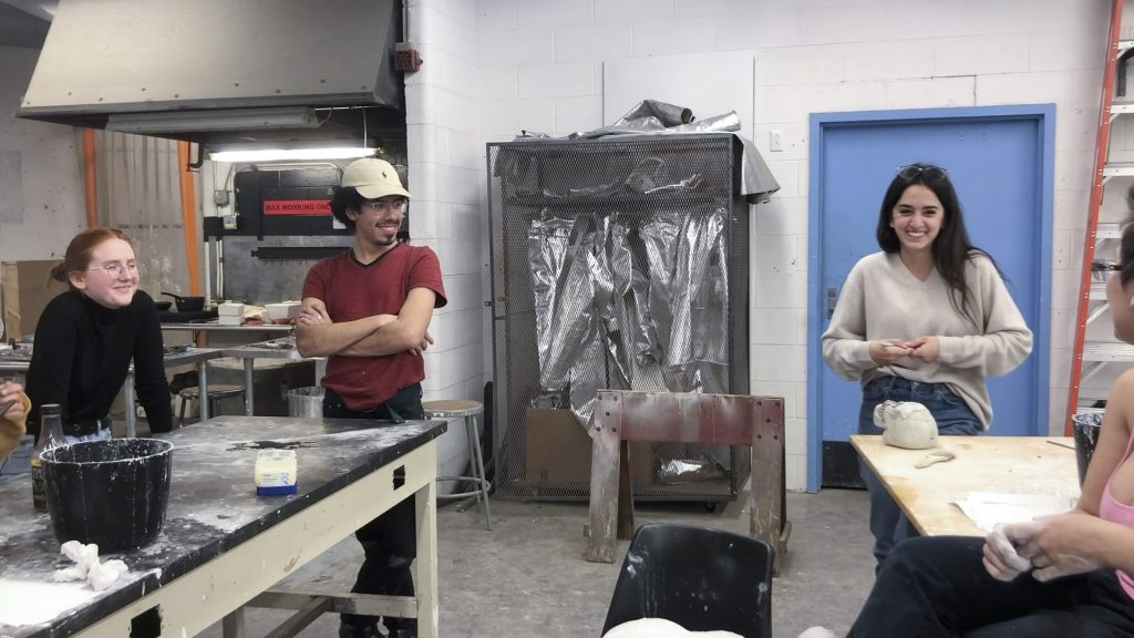 Danielle Russo laughs with studio arts classmates while in a studio class.