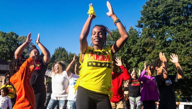 A yellow shirt-clad instructor from Wacheva's Dancing and Drumming Group leads participants through a Zumba dance on the Harvard Dance Stage at the 27th annual Westcott Street Cultural Fair. Wacheva is an organization that