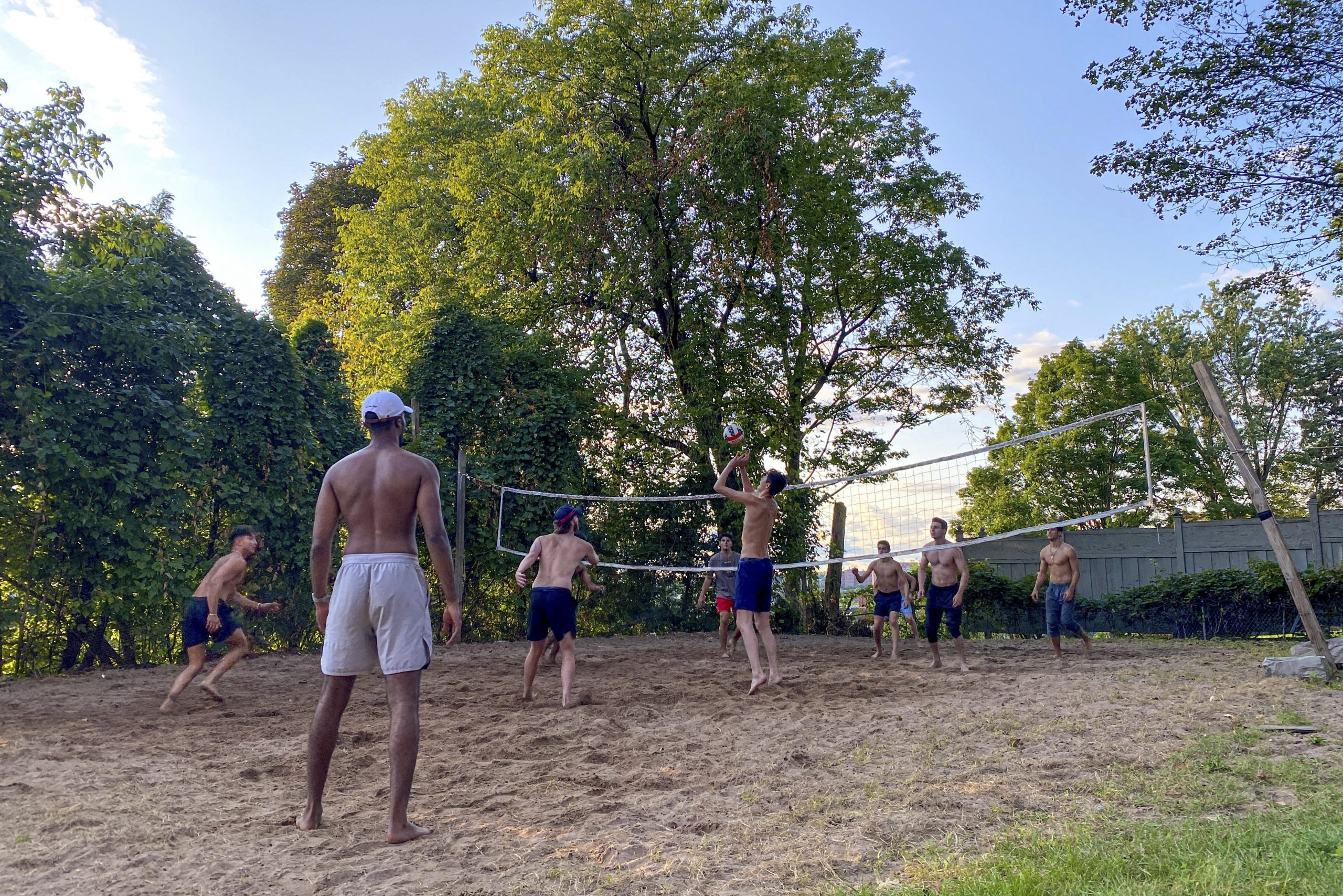 """Senior Harrison Stier sets the ball to his teammate in a game of beach volleyball outside the Delta Kappa Epsilon fraternity house. """"We only get this weather for a short amount of time, so we have to make the most of it,"""" Stier said."""