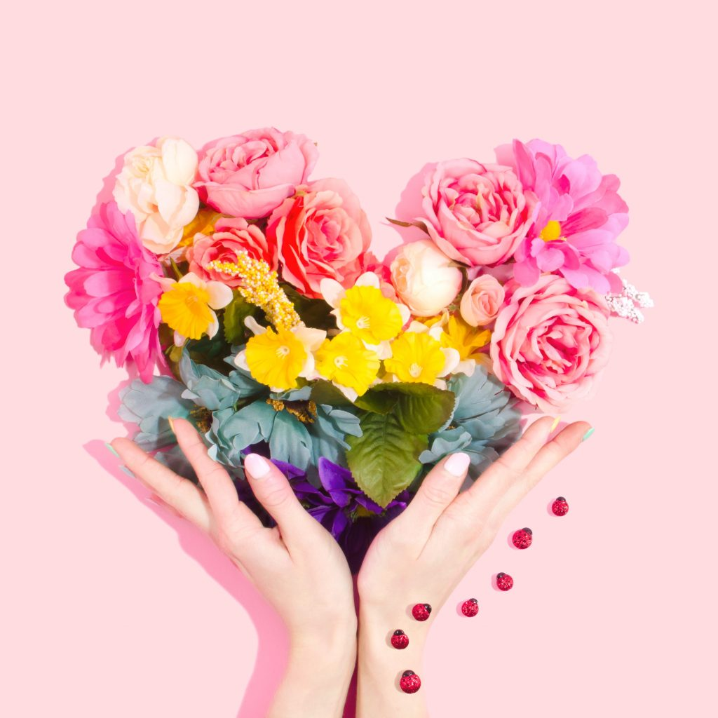 Two hands hold a bouquet of flowers.