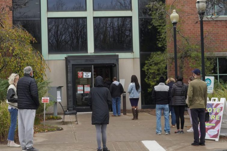 Voters wait outside of the early polling station in Dewitt, N.Y. on Oct. 31.