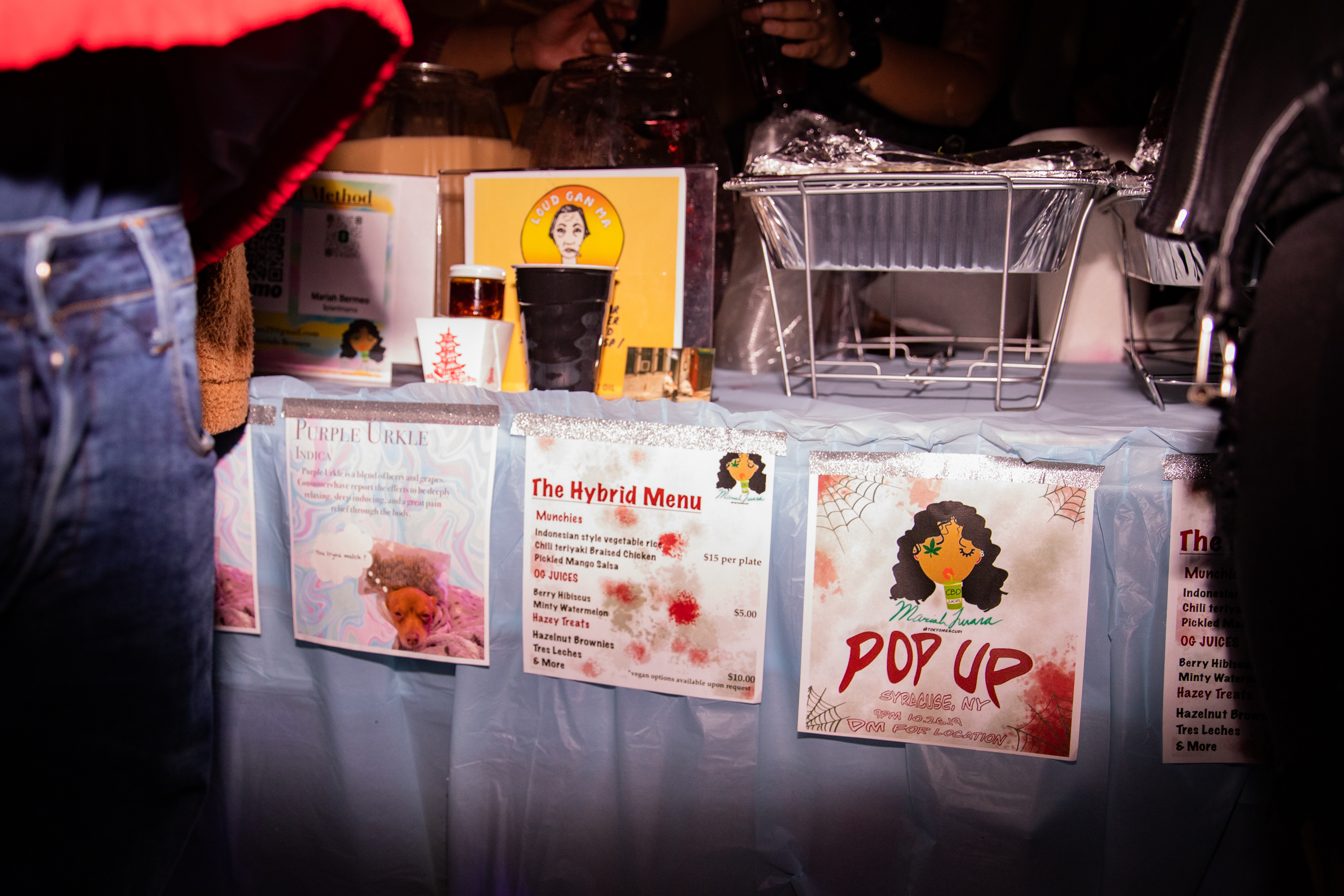 Placards display the menu for Mariah B's CBD pop-up food table at a party.
