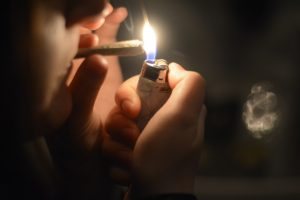 A Syracuse student lights a marijuana cigarette in their apartment.