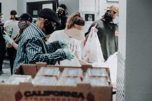 Volunteers help sort bags of food
