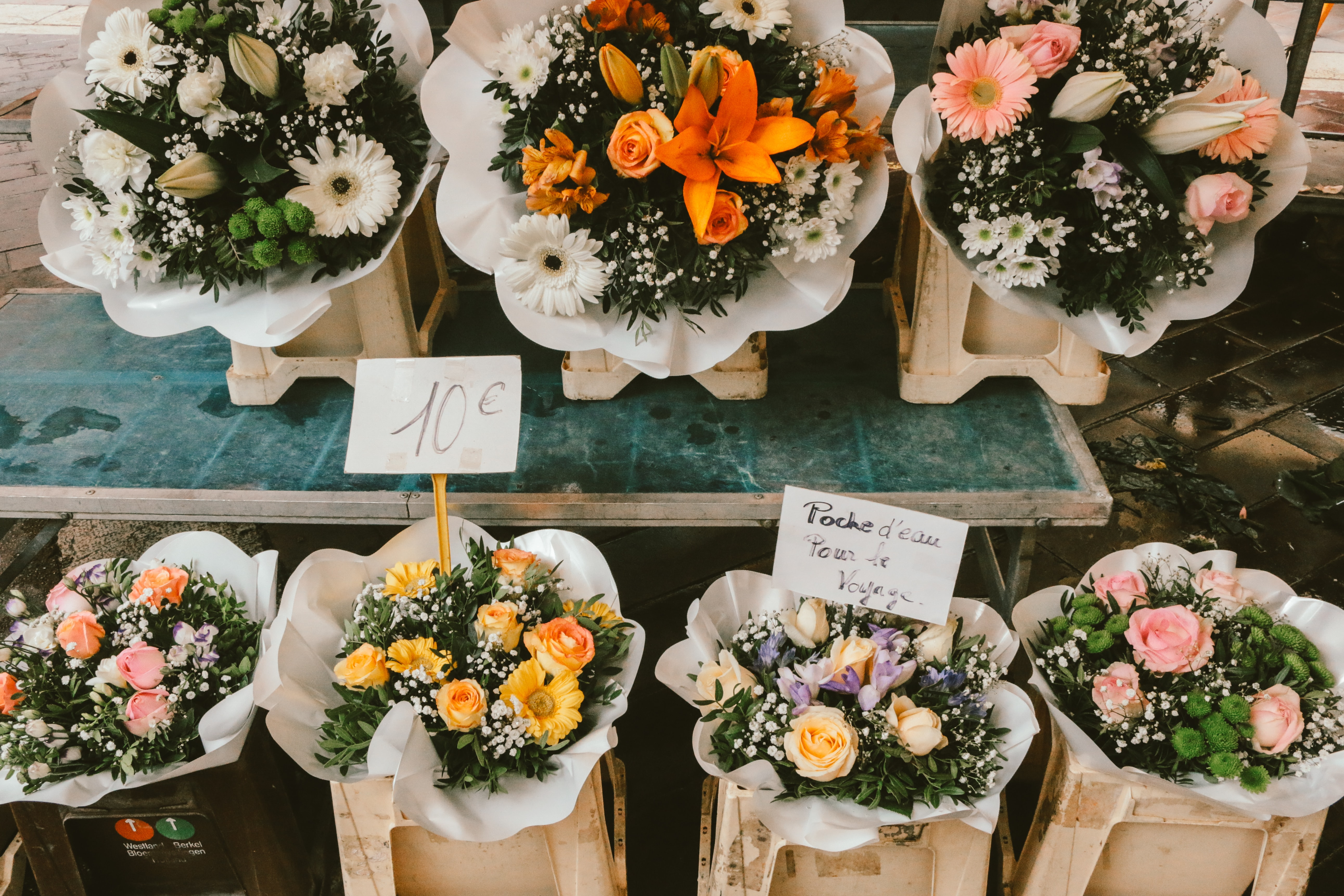 Bouquets of flowers sit side by side at a florist.