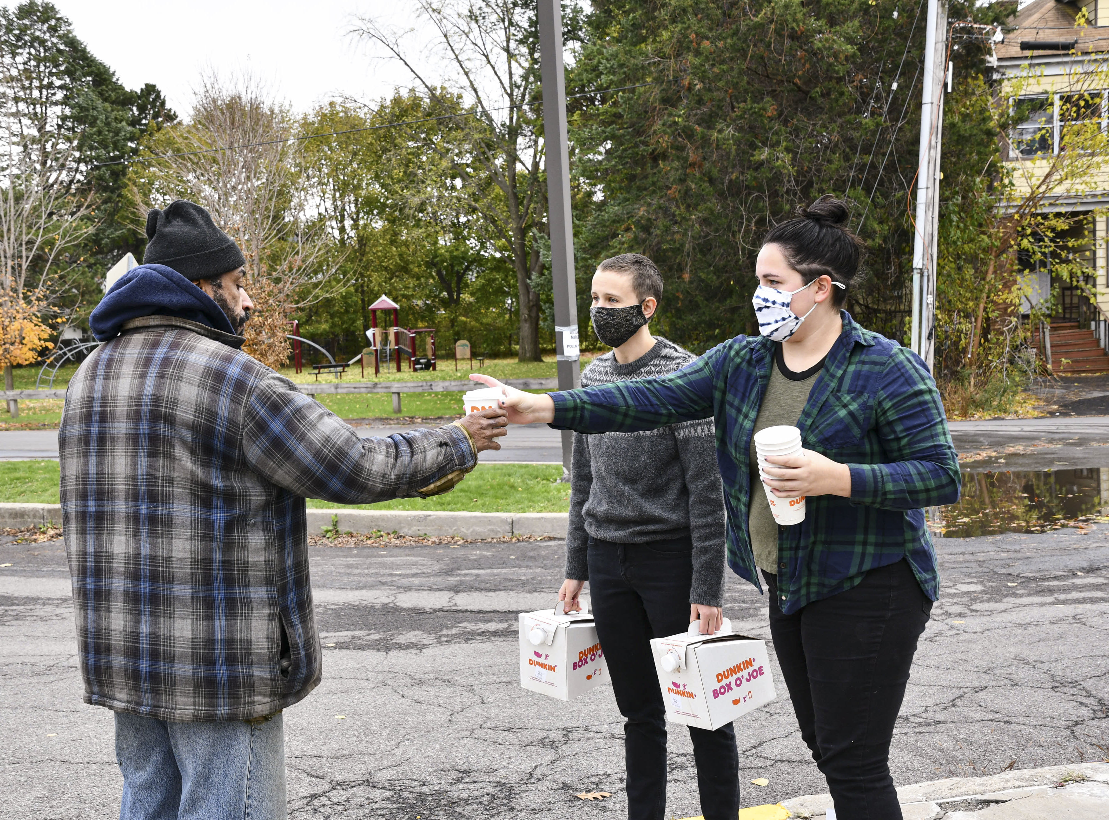 Lydia Dewing (right) and Luca Jurich (left) give a poll worker a cup of coffee on Election Day. According to Dewing, the two wanted to do something nice for voters and poll workers and plan to go to various polling places throughout Syracuse.