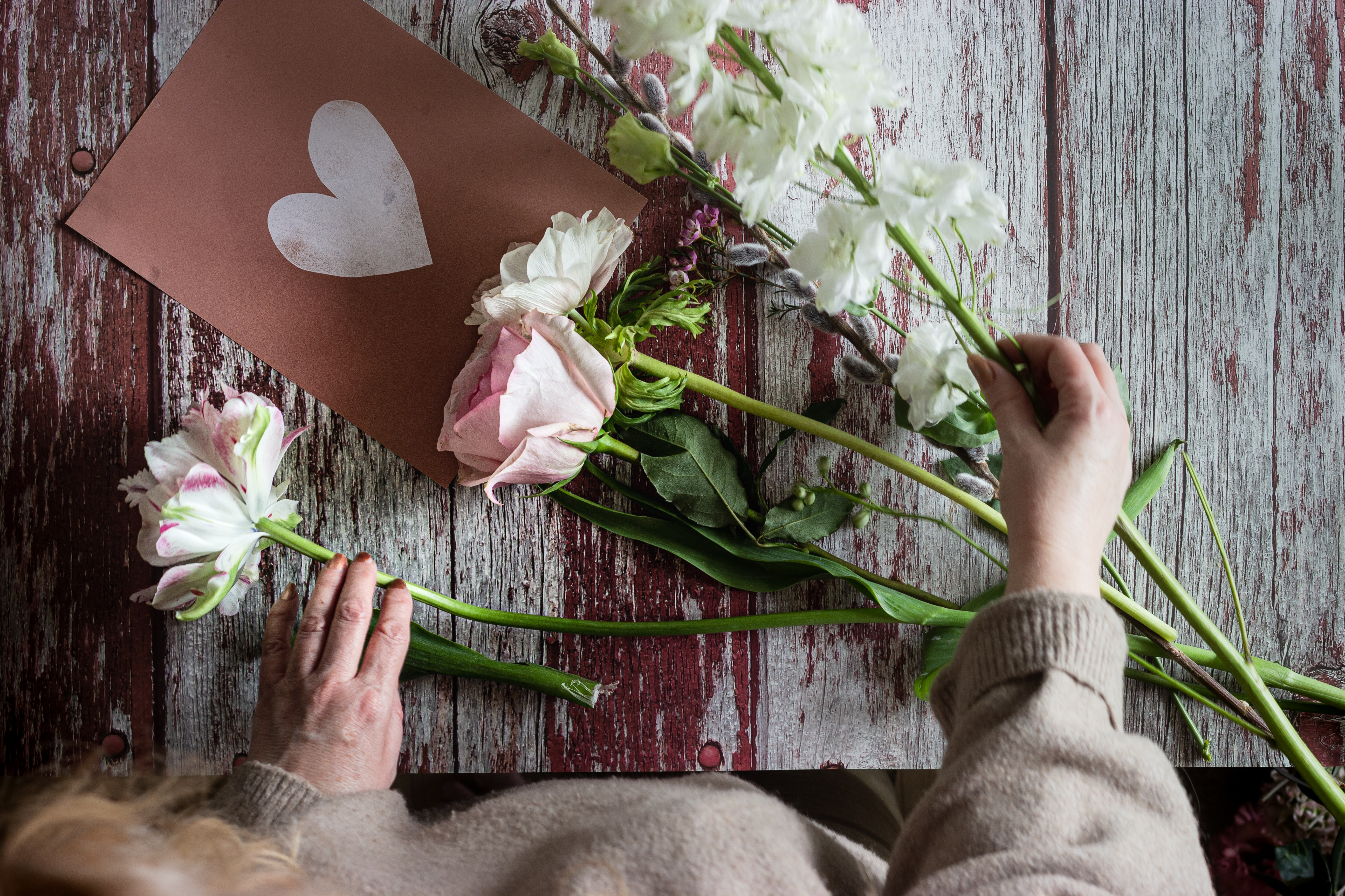 An individual places flowers around a handmade card with a heart drawn on it.