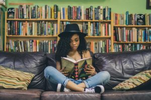 A person sits on a couch reading a book.