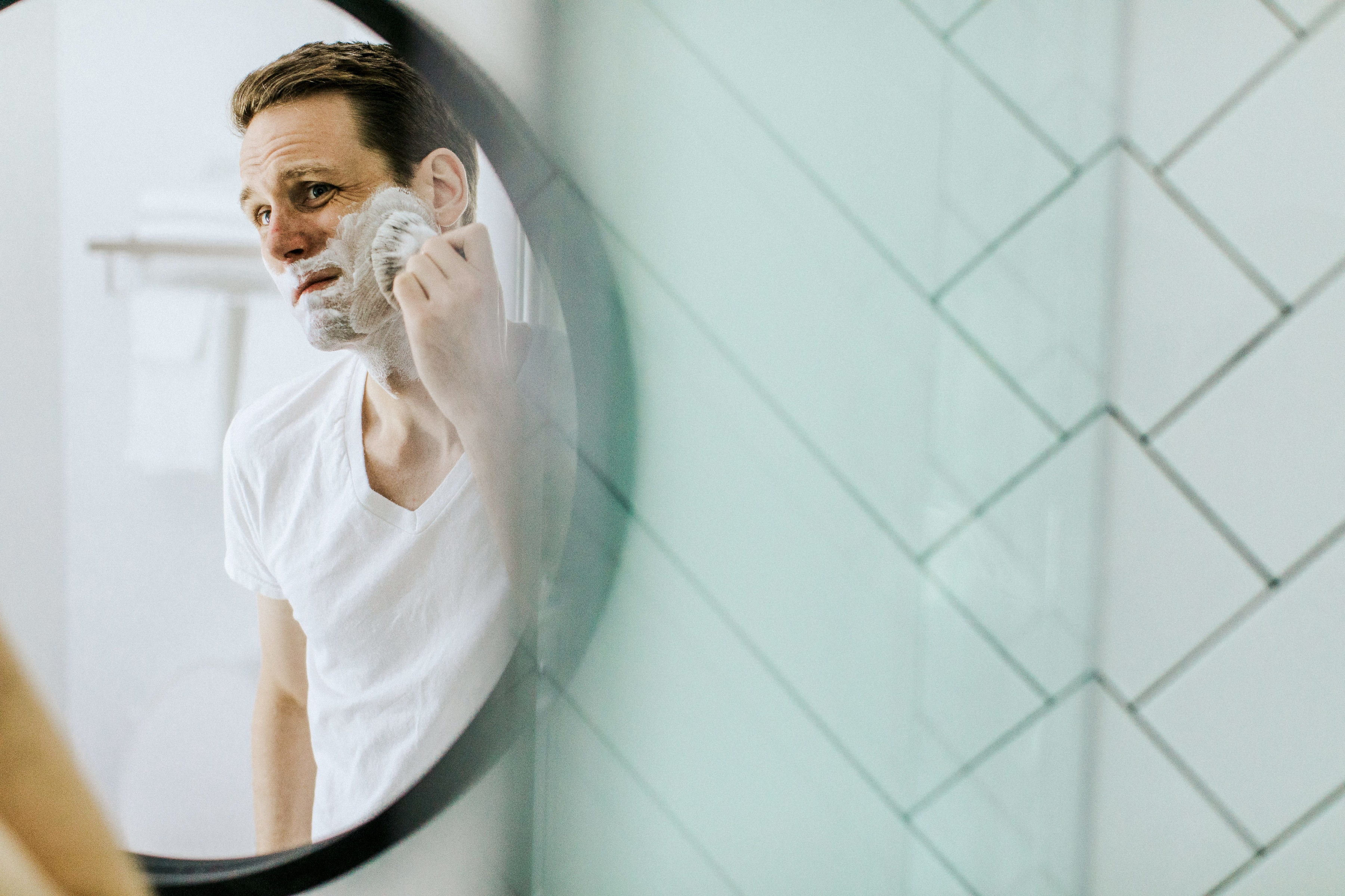 A person washes his face with a face brush.
