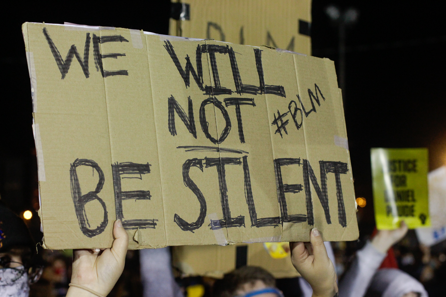 Protestors, blinded by police floodlights, chanted in front of the Public Safety Building on Friday, September 11, 2020. Many of the protestors' signs repeated the same few phrases.